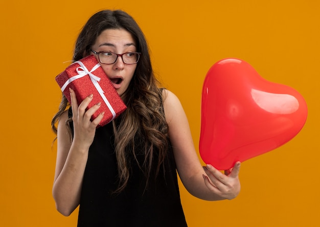 Young beautiful woman holding red balloon in heart shape and gift looking surprised and happy smiling cheerfully celebrating valentine's day