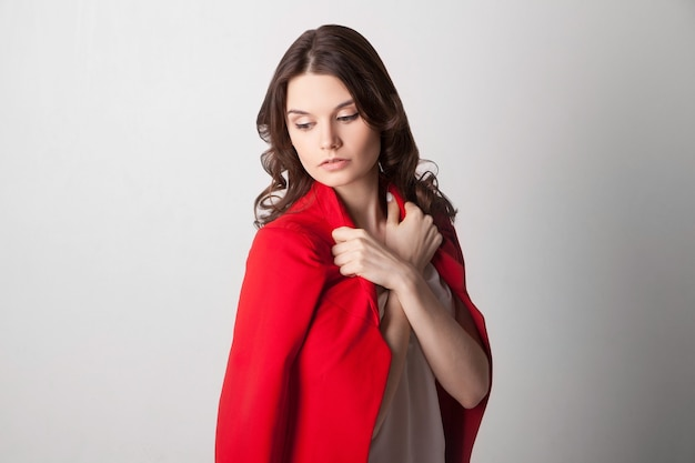 어깨에 빨간 재킷을 들고 젊은 아름 다운 여자. 아래를 내려다 보면서