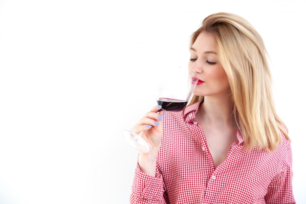 Young beautiful woman holding red wine glass on white