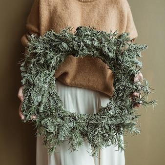 オリーブの壁にモミの枝で作られた丸い花輪フレームを保持している若い美しい女性。最小限のファッションのお祝いのクリスマスのお祝いのコンセプト。