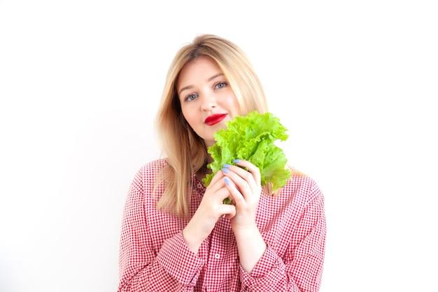 Молодая красивая женщина, держащая листья салата на белом фоне