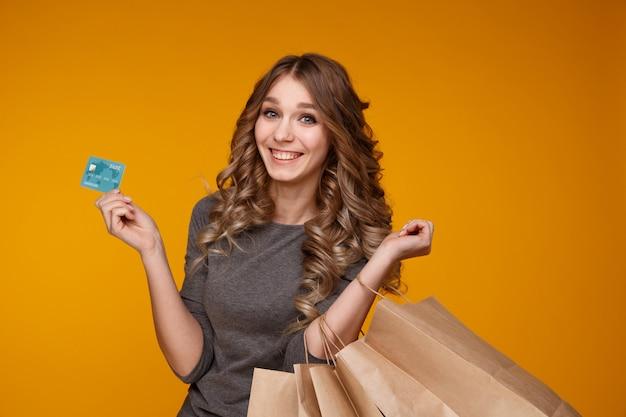 Молодая красивая женщина, держащая хозяйственные сумки и кредитную карту, изолированную на желтом фоне