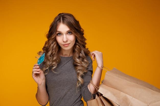 Молодая красивая женщина держит хозяйственные сумки и кредитную карту, изолированную над желтым