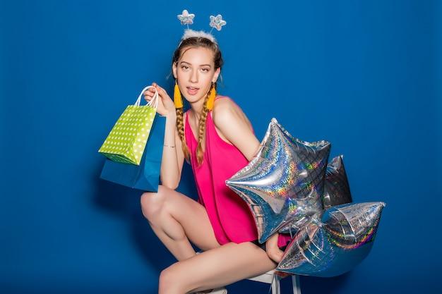 쇼핑백과 풍선을 들고 젊은 아름 다운 여자