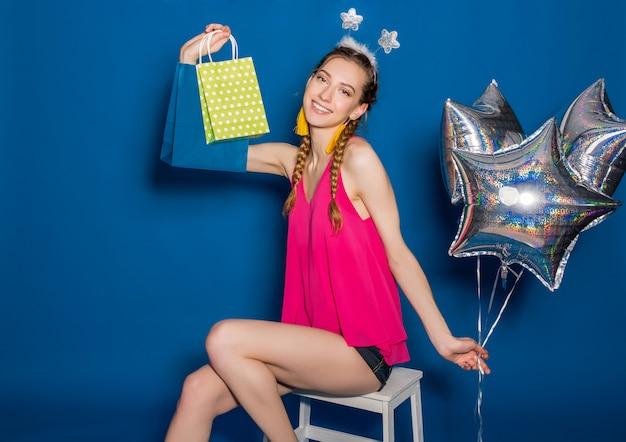 Молодая красивая женщина, держащая хозяйственные сумки и воздушные шары