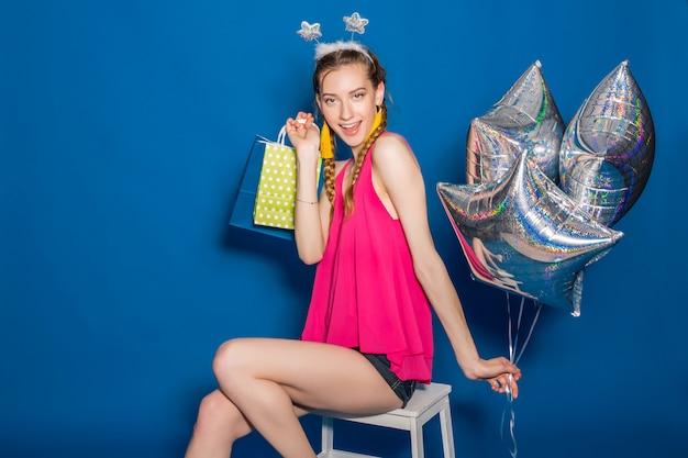 買い物袋や風船を保持している若い美しい女性