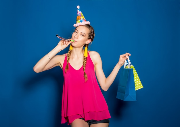 Молодая красивая женщина держит хозяйственные сумки и празднует