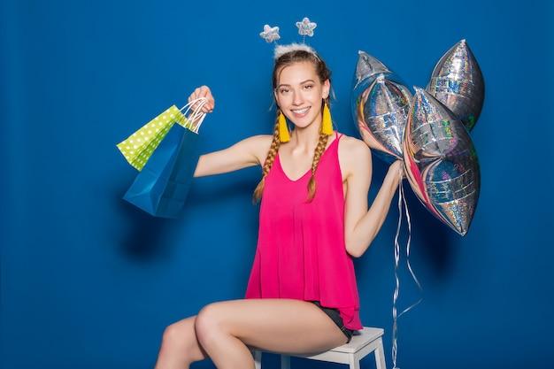 Giovane bella donna che tiene i sacchetti della spesa e gli aerostati