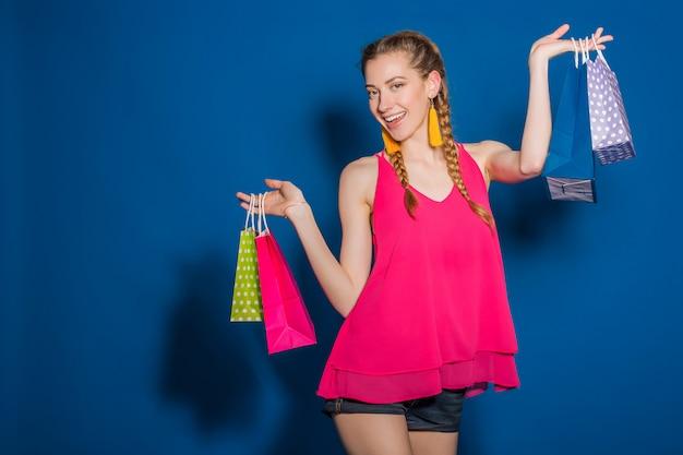 Молодая красивая женщина, держащая хозяйственные сумки