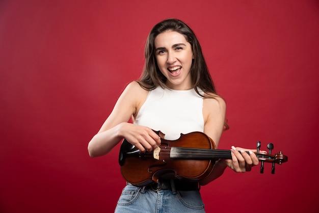 Giovane bella donna che tiene un violino