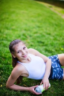 緑の芝生でトレーニングした後水のボトルを保持している若い美しい女性。