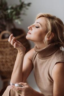 아름다운 젊은 여성은 손에 향수 한 병을 들고 손목에서 향기를 즐기면서 숨을 들이마십니다. 부드러운 선택적 초점입니다.