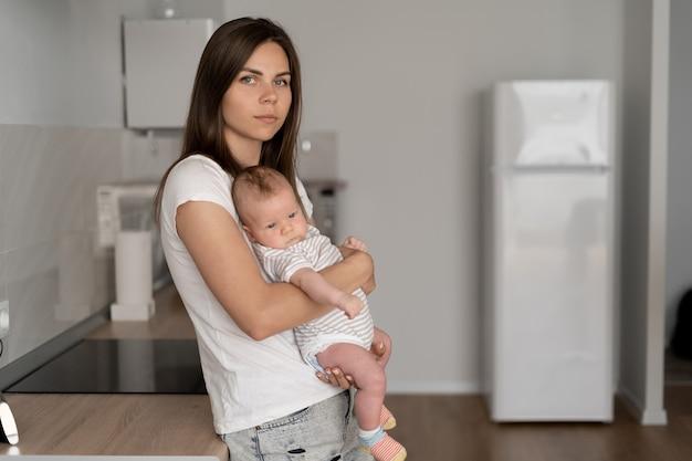 若い美しい女性は彼女の腕に小さな子供を抱きます。育児休業。幸せな家族、テキストのための場所。 Premium写真