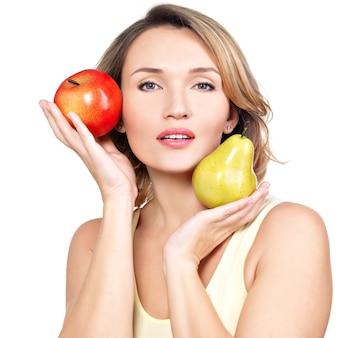 La giovane bella donna tiene la mela e la pera isolate su bianco.