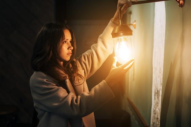 La giovane e bella donna tiene in mano una piccola lampada da parete