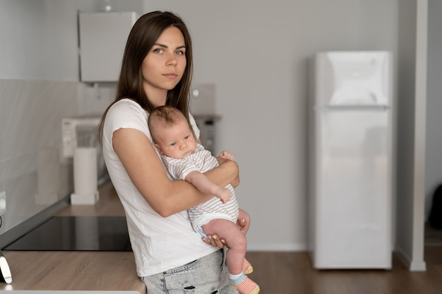 Young beautiful woman holds a small child in her arms. childcare leave. happy family, place for text.