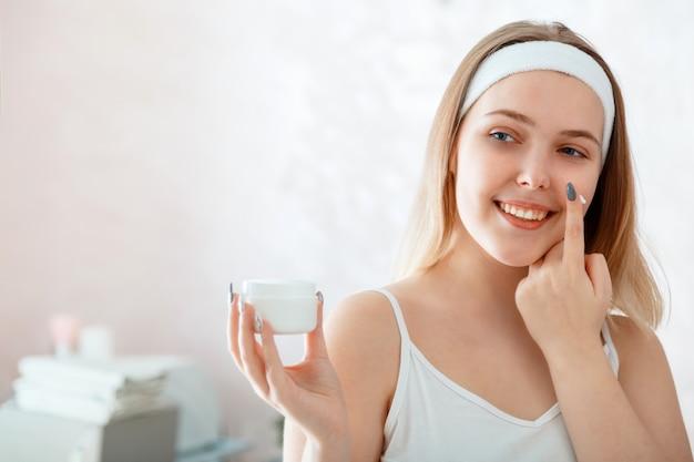 젊은 아름다운 여성은 흰색 병을 들고 욕실에 있는 얼굴에 크림을 바르고 보습 크림을 바르고 있습니다. 셀프 케어 아침 루틴. 집에서 뷰티 스파 트리트먼트. 여성은 얼굴 피부 스킨케어 미용 제품에 사용합니다.