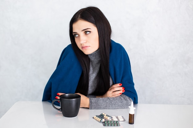 Young beautiful woman at home on white table feeling unwell and coughing as symptom for cold or bronchitis. healthcare concept.