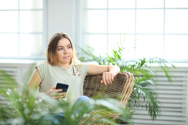 Young beautiful woman at home with plants