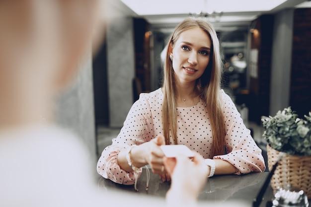 Гость отеля молодая красивая женщина оплачивает свое пребывание кредитной картой на стойке регистрации