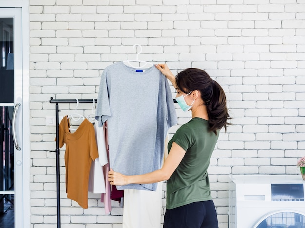 Young beautiful woman, housewife in casual wearing protective face mask hanging dry shirt with hanger on clothesline after washing near wash machine in laundry room on white wall.