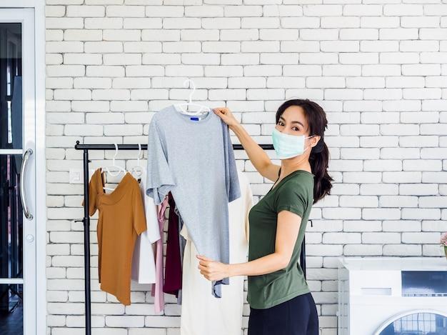 Молодая красивая женщина, домохозяйка в повседневной защитной маске, висящей на сухой рубашке с вешалкой на бельевой веревке после стирки возле стиральной машины в прачечной на белой стене.