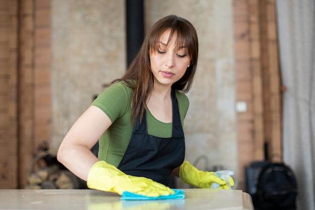 Молодая красивая женщина-домохозяйка в желтых резиновых защитных перчатках и черном фартуке убирает пыль, стирает стол, используя ткань из микрофибры. уборка по дому, концепция уборки