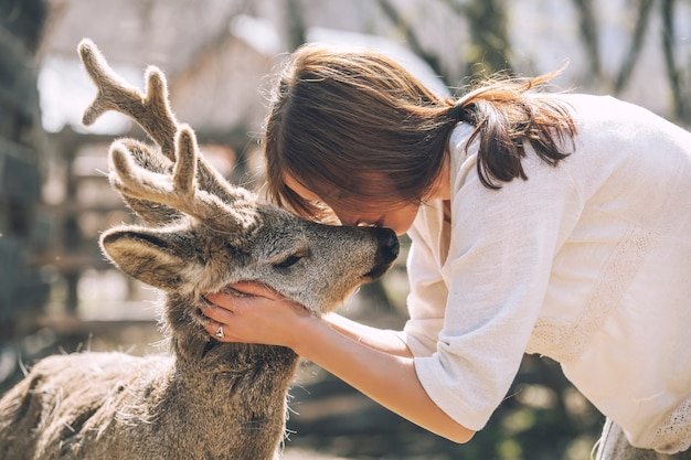 日差しの中で動物のノロジカを抱き締め、動物を保護する若い美しい女性