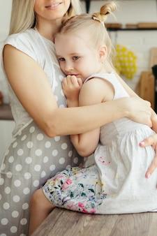 Молодая красивая женщина обнимает и целует свою милую маленькую дочь. тонировка.