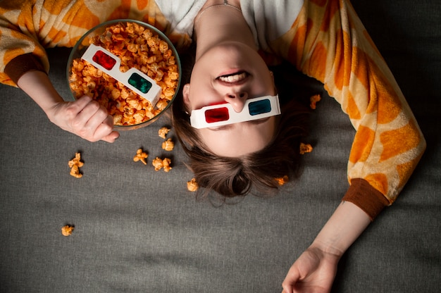 Молодая красивая женщина в 3d очках лежит на сером полу, ест сырный попкорн и смотрит фильм у себя дома на кровати