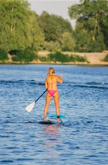川のsupボードでビキニの若い美しい女性