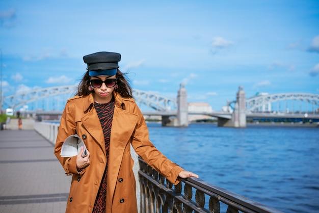 그녀의 손에 신문과 함께 포즈 제방에 코트에 검은 모자와 선글라스에 젊은 아름 다운 여자