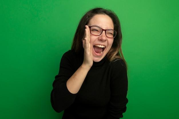 검은 터틀넥과 안경에 젊은 아름 다운 여자 행복하고 녹색 벽 위에 서있는 입 근처에 손으로 외치는 앞을보고 흥분