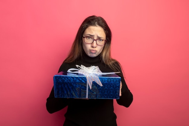 검은 터틀넥과 선물 상자를 들고 안경에 젊은 아름 다운 여자 앞 wirh 슬픈 표정을보고 분홍색 벽에 서 불쾌한