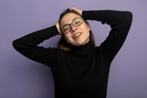 검은 터틀넥과 안경에 젊은 아름 다운 여자는 보라색 벽 위에 서 웃는 그녀의 머리에 손으로 전면 행복하고 긍정적 인 찾고