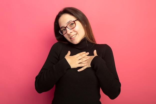 검은 터틀넥과 안경에 젊은 아름다운 여자가 분홍색 벽 위에 서있는 긍정적 인 감정을 느끼는 그녀의 가슴에 손을 잡고 앞을보고