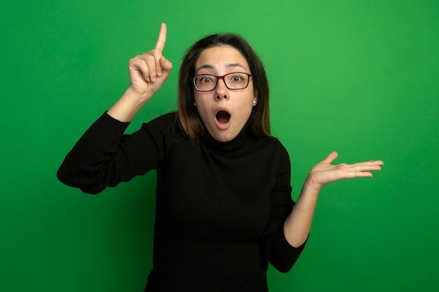 검은 터틀넥과 안경에 젊은 아름 다운 여자 놀라게하고 녹색 벽 위에 서있는 팔로 뭔가를 제시하는 검지 손가락을 보여주는 놀라움