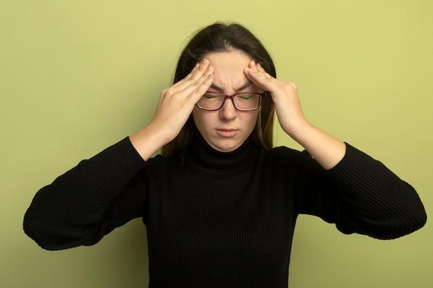 검은 터틀넥과 안경에 젊은 아름 다운 여자는 가벼운 벽 위에 서있는 두통으로 고통받는 그녀의 사원을 만지고 앞에서보고