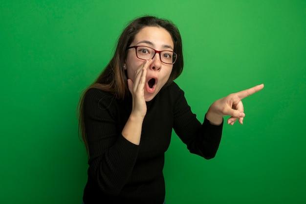 검은 터틀넥과 안경에 젊은 아름 다운 여자는 녹색 벽 위에 서있는 측면에 손가락으로 깜짝 속삭이는 수군 pointign를 찾고