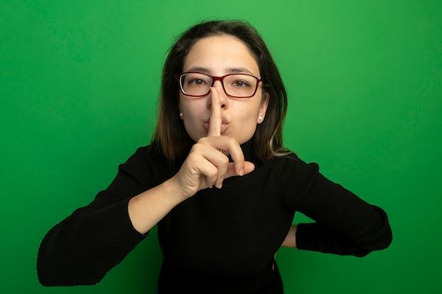 검은 터틀넥과 안경에 젊은 아름 다운 여자, 녹색 벽 위에 서있는 입술에 손가락으로 침묵 제스처를 만드는