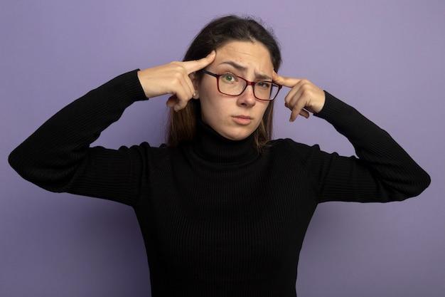 보라색 벽 위에 서있는 작업에 집중하려고 노력하는 그녀의 사원에서 손가락으로 가리키는 검은 터틀넥과 안경에 젊은 아름 다운 여자