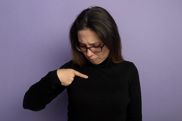 검은 터틀넥과 보라색 벽 위에 서서 혼란스러워하는 자신의 검지 손가락으로 가리키는 안경에 젊은 아름 다운 여자
