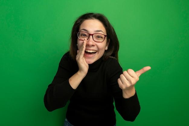 검은 터틀넥과 녹색 벽 위에 서있는 측면에 손가락으로 속삭이는 수군 pointign 미소 안경에 젊은 아름 다운 여자