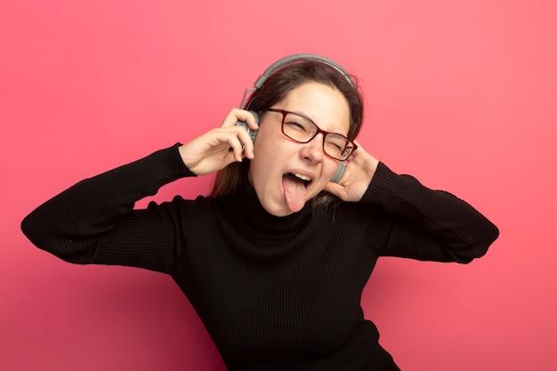 검은 터틀넥과 헤드폰 행복하고 흥분 분홍색 벽 위에 서 혀를 튀어 나와 안경에 젊은 아름 다운 여자