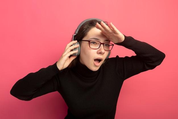 ピンクの壁の上に立っている頭の上に手で遠くを見ているヘッドフォンと黒いタートルネックとメガネの若い美しい女性