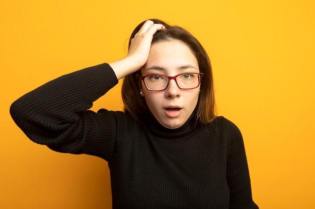 Молодая красивая женщина в черной водолазке, смотрящая вперед, обеспокоена и смущена рукой на голове, стоящей над оранжевой стеной