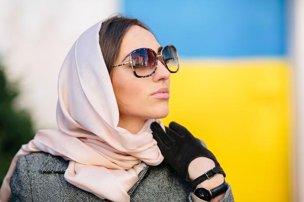 Молодая красивая женщина в пальто, сидя на скамейке в парке
