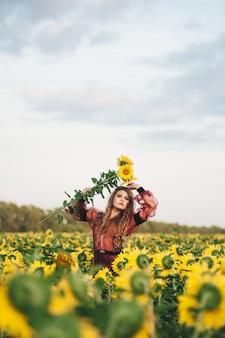 Молодая красивая женщина в платье среди цветущих подсолнухов. агро-культура.