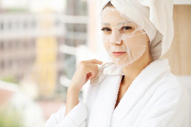 얼굴 마스크, 피부 관리에에서 젊은 아름 다운 여자.