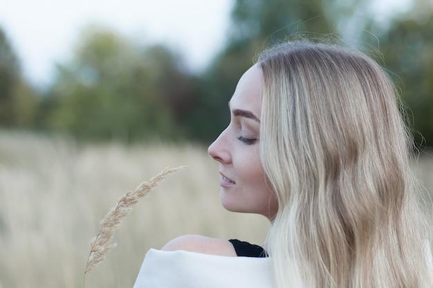 Молодая красивая женщина в поле на закате. гулять на свежем воздухе.